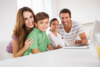 Happy family looking at the camera with a laptop in kitchen