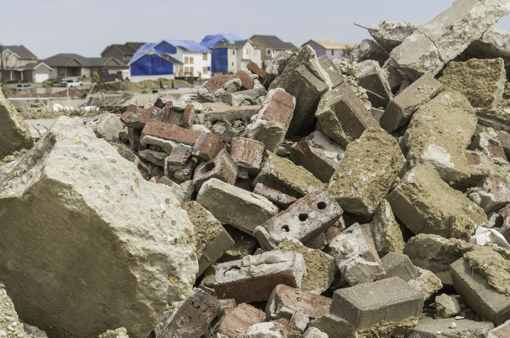 Rubble from destroyed homes remains heaped up in neighborhood where other houses undergo repair during recovery more than 4 months after a tornado in Washington, Illinois, USA