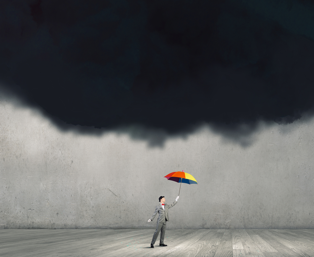 Businessman standing with umbrella under black cloud