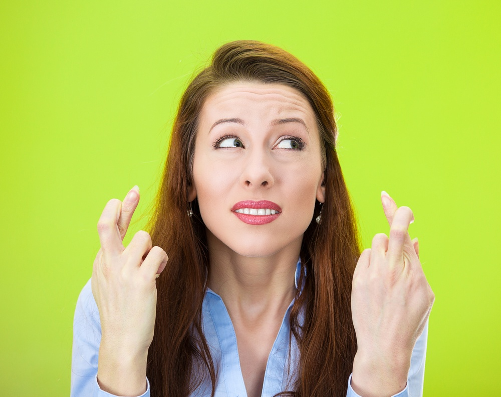 Closeup portrait of sad, worried, concerned woman, student, mother crossing her fingers hoping, asking for best, isolated green background. Human face expressions, emotions, feeling, attitude reaction