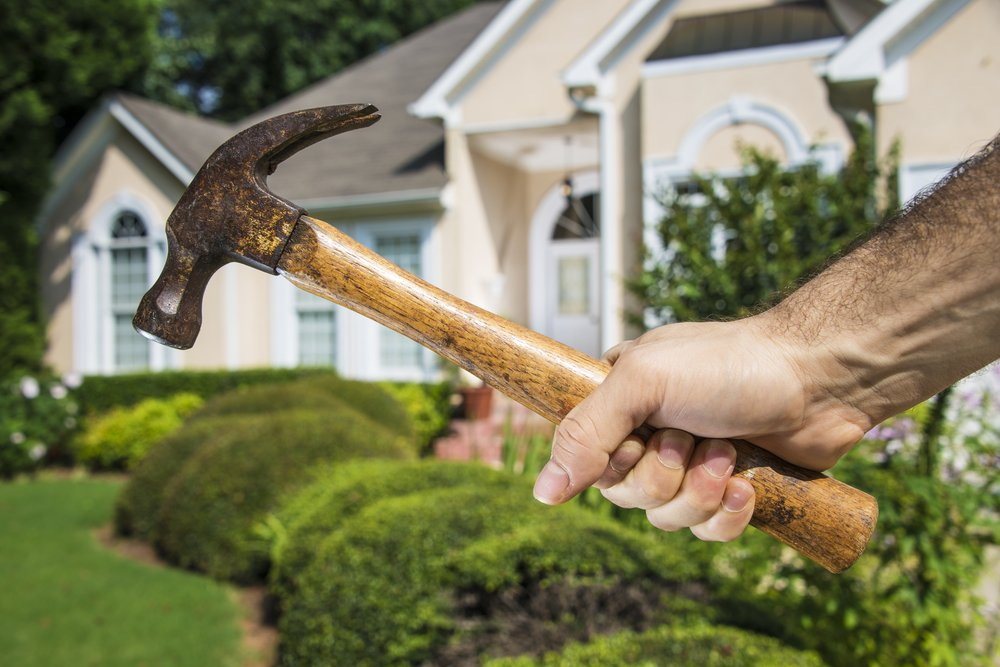 Mans hand holding hammer in front of a house indicating home improvement and maintenance.