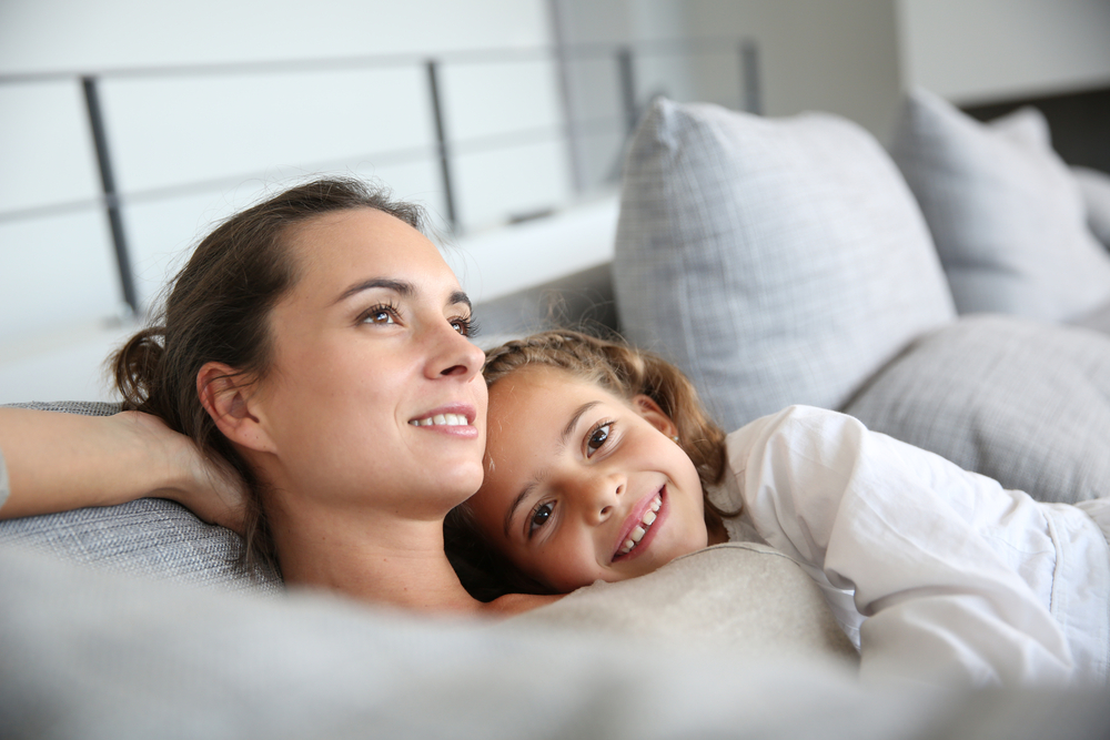 Mom and little girl relaxing in sofa